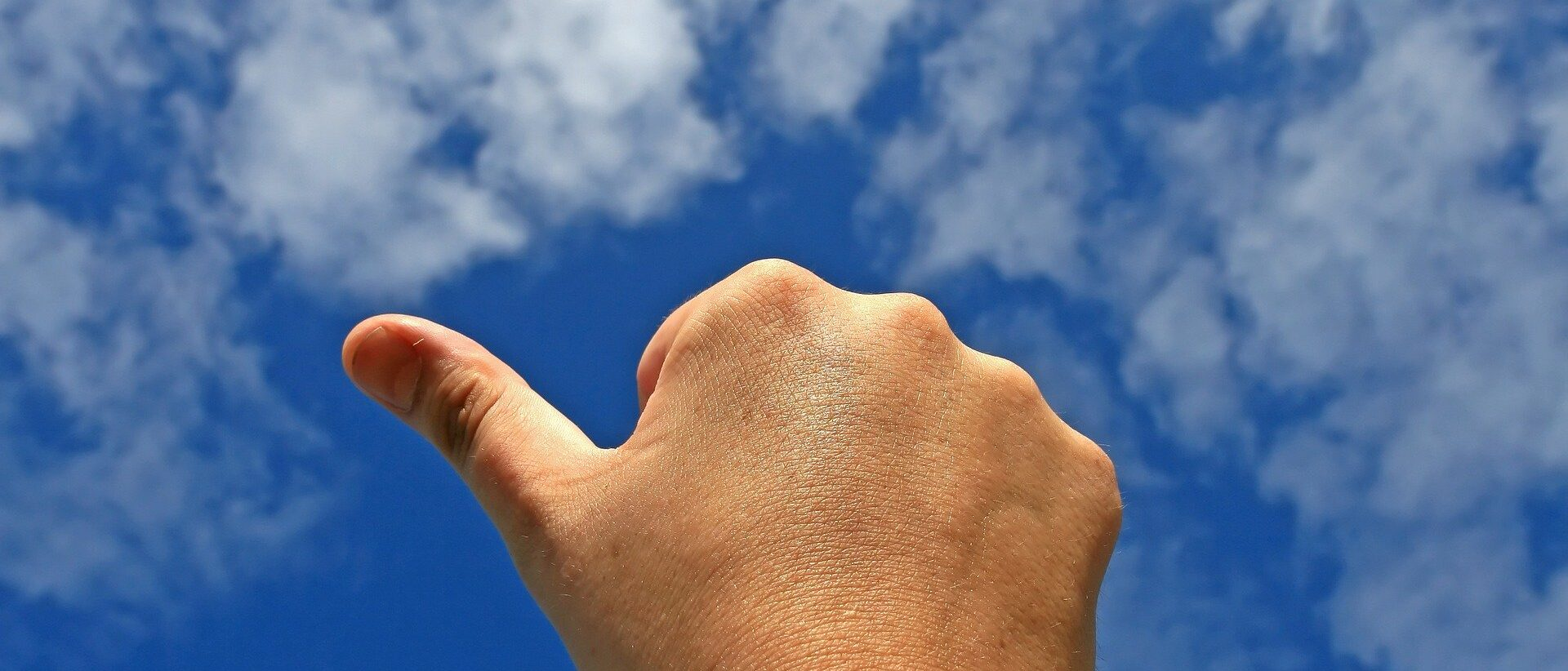 thumb in the air on a blue sky